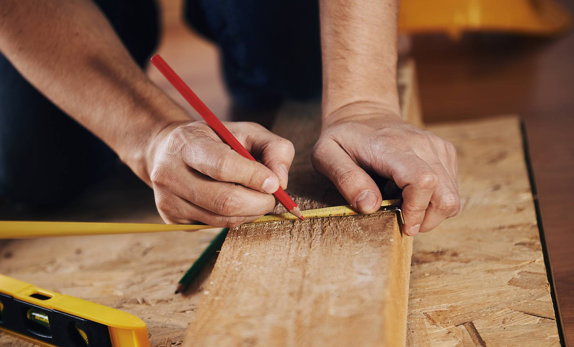 carpenter drawing out markings on wood